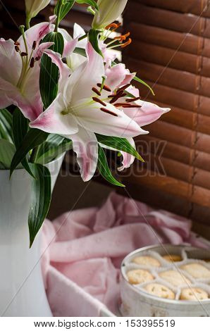 Pink and white lilies in a vase. The rays of the sun through the wooden blinds. Romantic Breakfast. Selective focus.