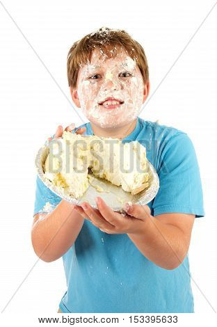 Funny Eleven Year Old Boy with a Cream Pie.  He is holding the wrecked pid and has cream all over his face