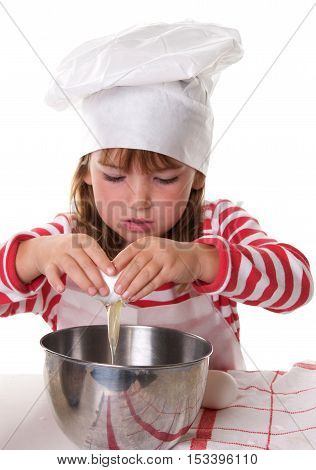 Cute Little Girl With a Chef Hat and Apron Baking.  She is cracking an egg into a bowl