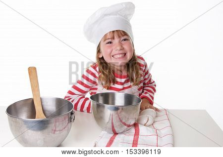 Cute Little Girl With a Chef Hat and Apron Baking.  She has a big happy smile
