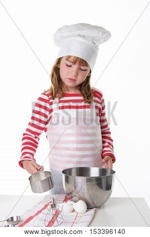 Cute Little Girl With a Chef Hat and Apron Baking.  She is about to add an ingredient with a measuring cup.