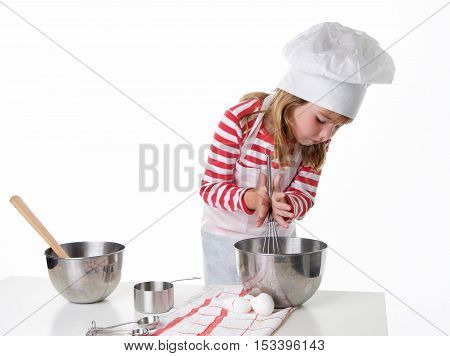 Cute Little Girl With a Chef Hat and Apron Baking.   She is busy whisking ingredients in a metal bowl.