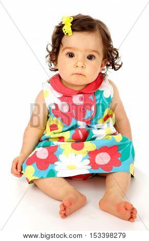 Cute baby girl on a white background wearing a pretty colorful dress.  She has a very cute soft frown expression