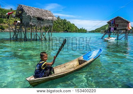 Semporna,Sabah-Sept 10,2016:Sea Gypsy kids on a boat on at Bodgaya island,Semporna,Sabah.This sea gypsies kids are given a net & taught to catch fish,octopus & lobsters off their unique handmade boats