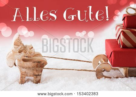 Moose Is Drawing A Sled With Red Gifts Or Presents In Snow. Christmas Card For Seasons Greetings. Red Christmassy Background With Bokeh Effect. German Text Alles Gute Means Best Wishes