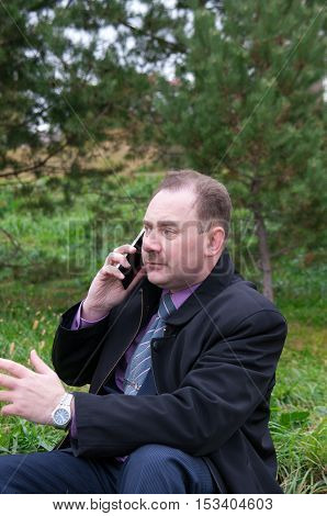 Man talking on the phone gesturing hand on the background of fir trees