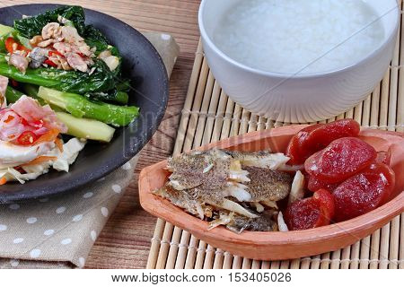 Close up of rice gruel and  side dish as shredded of fried sun-dried fish ,Chinese sausage,spicy salted egg salad and fried kale with salted fish. Selective focus.