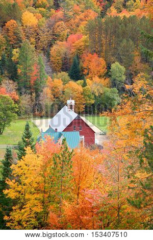 Red barn in  Vermont rural side surrounded by fall foliage