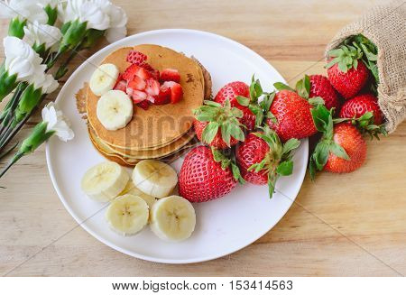 breakfast pancake with strawberry and slice of banana on whie place with wooden background