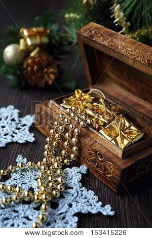 Christmas-tree decorations and goldish garland in carved wooden casket. Focus selective