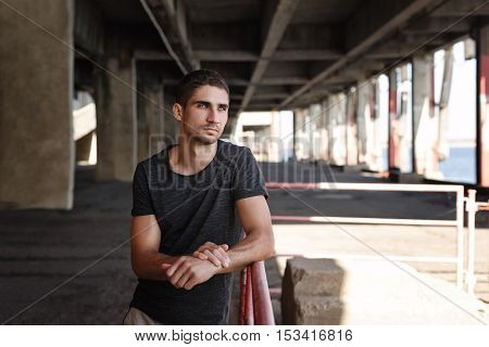Portrait of a man in a T-shirt in the urban space. He looks away and thinks about lofty matters.