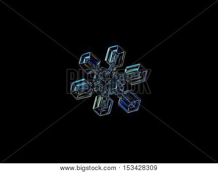 Snowflake isolated on black background: macro photo of real snow crystal, captured on glass surface with LED back light. This is medium size snowflake, resembling duck feet, or gecko's paw.
