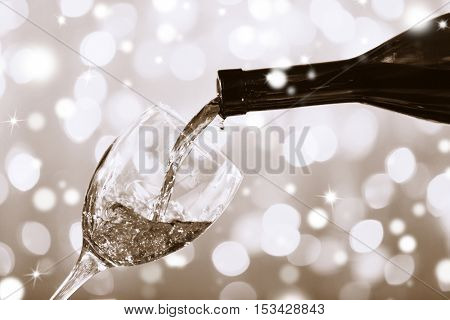 Pouring wine into glass on bokeh background, closeup. Black and white photo. Christmas celebration concept.