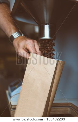 Close-up of unrecognizable worker filling paper package with roasted coffee beans