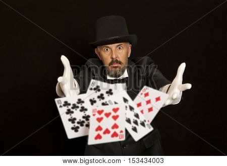Magician show with playing cards. Isolated on black background