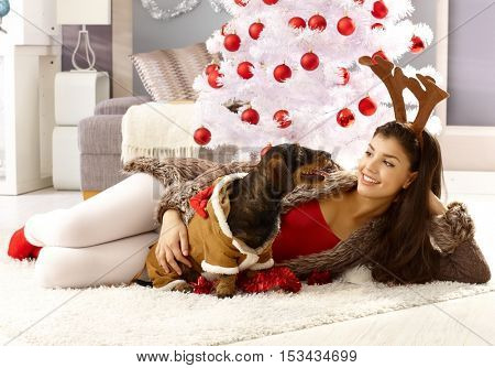 Young woman and dog celebrating christmas at home.