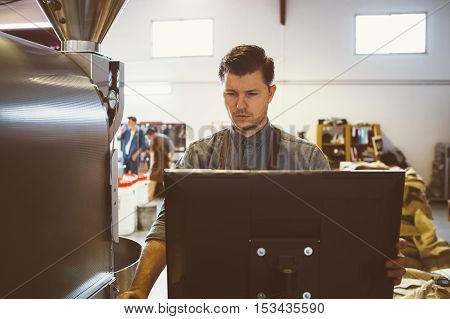 Portrait of serious coffee roaster using computer at factory
