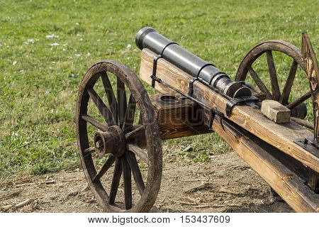 Man made wooden cannon replica on old wheels.