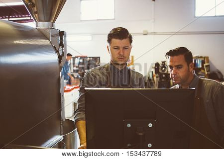 Two professional coffee roasters using computer at factory