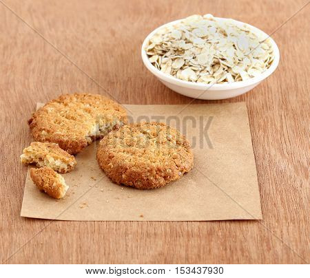 Homemade, healthy food oatmeal cookie and in the background is oats in a bowl.