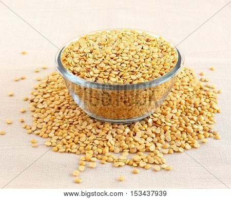 Indian food toor dal, also known as split pigeon pea, rich in proteins, in a glass bowl.