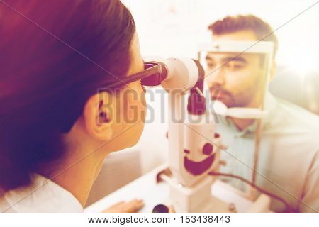 health care, medicine, people, eyesight and technology concept - close up of optometrist with slit lamp checking patient vision at eye clinic or optics store