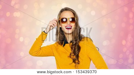 people, style and fashion concept - happy young woman or teen girl in casual clothes and sunglasses over rose quartz and serenity lights background