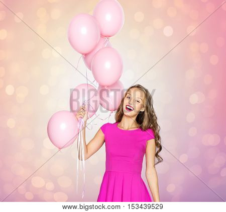 people, holidays, birthday and party concept - happy young woman or teen girl in pink dress with helium air balloons over rose quartz and serenity lights background