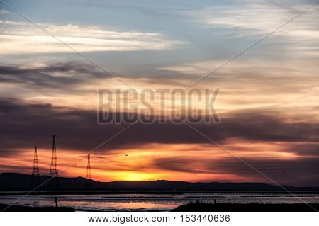 Silhouette Sunset over Alviso marina County Park, San Francisco Bay Area, California, USA. Intensive colored Sunset of hills and power transmission towers in the bay area.