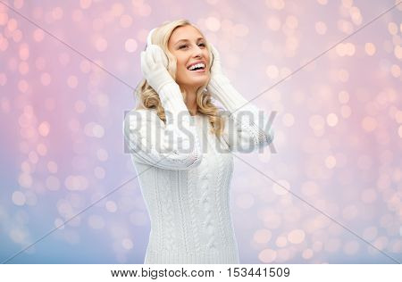 winter, fashion, christmas and people concept - smiling young woman in earmuffs and sweater over rose quartz and serenity lights background