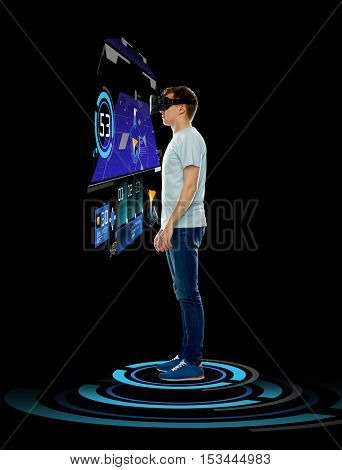 3d technology, gaming, augmented reality, cyberspace and people concept - happy young man in virtual reality headset or 3d glasses with gps navigator projection over black background