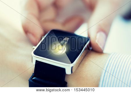 business, technology, communication, conection and people concept - close up of woman hands with lightbulb icon on smartwatch screen