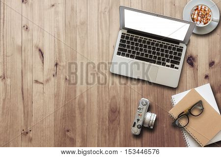 Flat lay of workspace wooden desk with laptop coffee camera eyeglasses and notebook