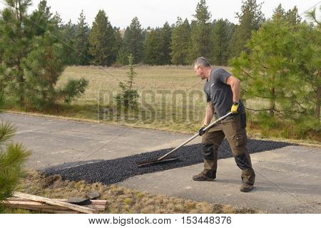 Colbert, WA - October 24, 2016: Workers of Black Diamond Asphalt Paving, LLC., repairing patches in a private road/driveway