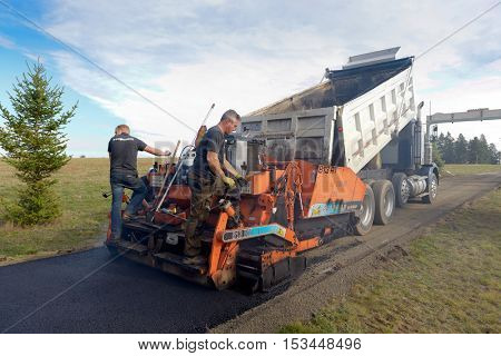 Colbert, WA - October 24, 2016: Workers from Black Diamond Asphalt Paving, LLC., repairing patches and re-paving a private road/driveway