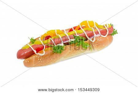 Hot dog with frankfurter mustard mayonnaise and vegetables in bun with sesame seeds on a light background