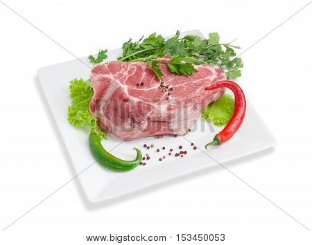 Piece of a fresh uncooked pork neck green and red chili black and red pepper lettuce parsley and cilantro on a white square dish on a light background