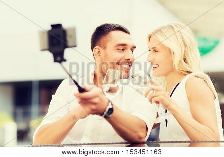 love, date, technology, people and holidays concept - happy happy couple taking picture with smartphone on selfie stick and clinking glasses at city street cafe or restaurant