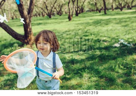 happy toddler boy catching butterflies with net on spring walk in the garden. Outdoor seasonal activities.