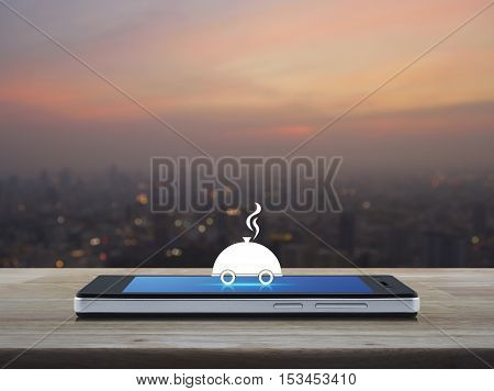 Restaurant cloche flat icon on modern smart phone screen on wooden table over blur of cityscape on warm light sundown Food delivery concept