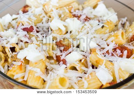Baked tortiglioni pasta with tomato sauce mozarella cheese and parmesan cheese in glass bowl