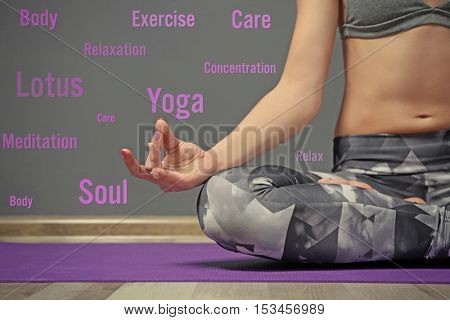 Young woman practising yoga at home. Yoga and health care concept.