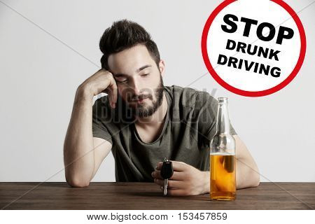 Drunk young man with car key and beer bottle at bar. Sign with text STOP DRUNK DRIVING on background.