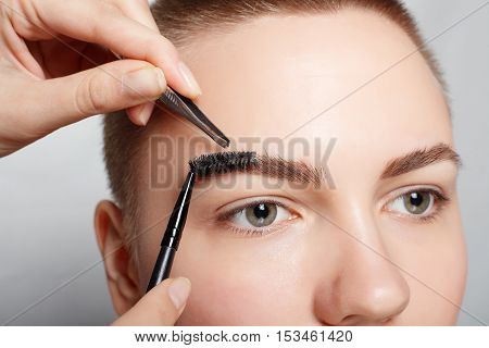 Young woman with short hair plucking eyebrows with tweezers close up studio shot. on a light background. beauty shot .Closeup part of face woman plucking eyebrows depilating with tweezers.