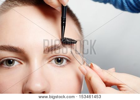 Young woman with short hair plucking eyebrows with tweezers close up studio shot. on a light background. beauty shot .Closeup part of face woman plucking eyebrows depilating with tweezers. poster