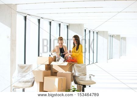 Young businesswomen untangling cords while standing by cardboard boxes in office