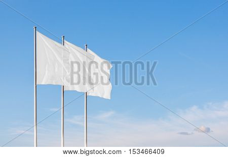 Three white blank flags waving in the wind against cloudy sky. Perfect mockup to add any logo symbol or sign