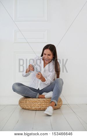 An attractive young Caucasian woman in casual clothing is radiant with the joyful emotions while playing on tablet and sitting on a hassock
