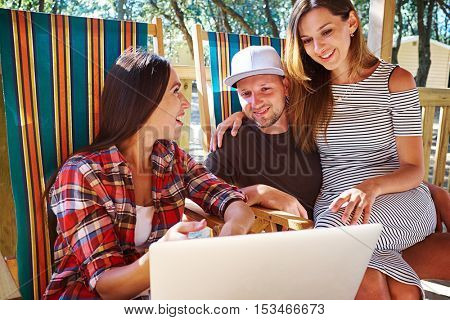 Mid shot of the group of friends who are spending time together during the vacation. Sudden and unexpected appearance. Woman shows something at the screen of the laptop.