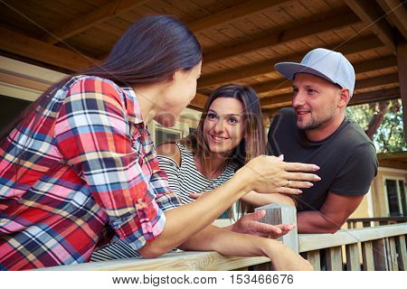 Close-up of a group of friends who are discussing something outside. Standing on the porch of the resting house. Women wearing striped and checked patterns of light summer clothes
